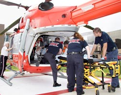 Emergency personnel loading a pateint into a helicopter. Credit: Federal Emergency Management Agency.
